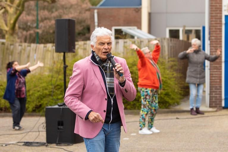 Ben Cramer zingt Baarnse ouderen toe vanaf ijskoude parkeerplaats; 'Kunnen jullie het horen binnen? Zet anders je gehoorapparaatje wat harder'