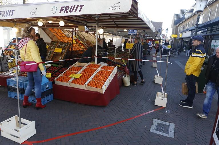 Surrealistisch beeld: Met mondkapjes naar de zaterdagmarkt. Dankzij kratjes en plakband blijven klanten keurig op afstand [video]